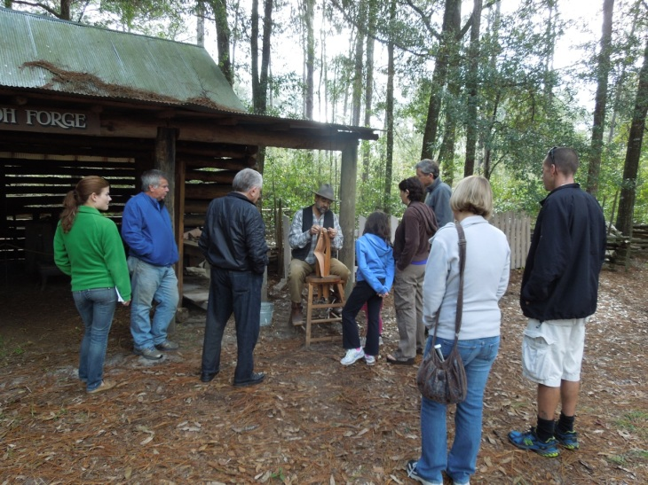 Art demonstrating hand stitching at the Morningside Nature Park Cane Boil while others watched the UF/FSU football game.